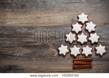 Christmas background with gingerbread cookies,christmas lights and spices on the old wooden board