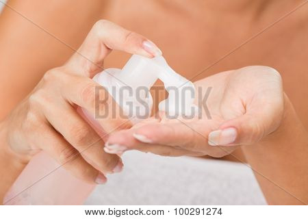 poster of Close-up of moisturizing foam cleaning face in the hands of a young woman unrecognizable face with a underwear. Selective focus.