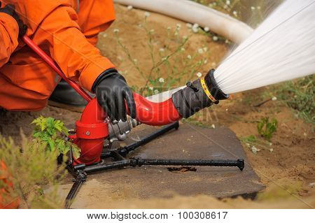 Fire Hose In Actions Pouring Water Operated By Fireman In Orange Uniform