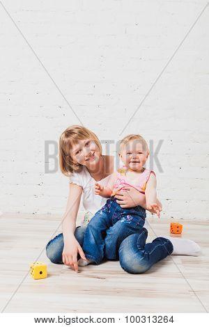 Smiling kids sitting on floor