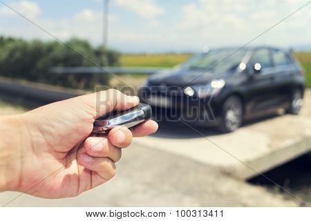 closeup of a young man unlocking the doors of his car with the control remote key, outdoors, with a filter effect