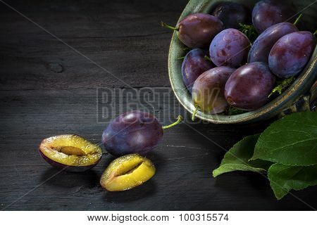 Plums In A Pottery Bowl And On Dark Rustic Wood, One Plum Is Halved