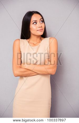 Portrait of happy thoughtful woman standing with arms folded and looking away