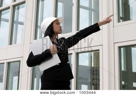 Female Engineer Pointing At Construction