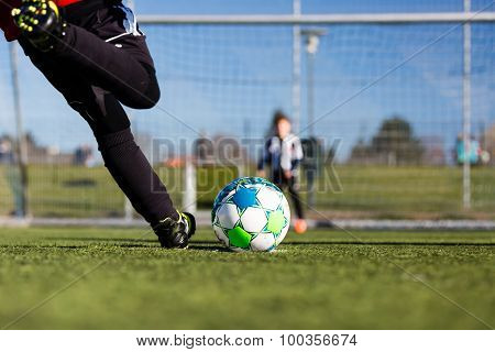 Close-up of young soccer player taking a penalty kick against a young blurred boy acting as goalie in the goal. poster