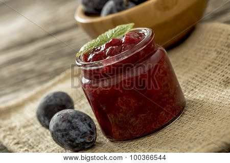 Home made plum jam in a jar and two plums next to it sitting on burlap sac with wooden bowl full of plums in background. poster