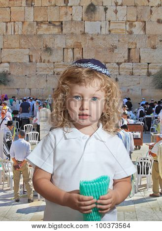 The Jewish holiday of Sukkot. Adorable little boy with long blond curls and blue eyes in  knitted skullcap. He stands at main Jewish shrine - the Western Wall of Temple