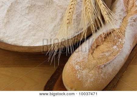 Crusty Baguette Bread With Wooden Bowl Full Of Flour