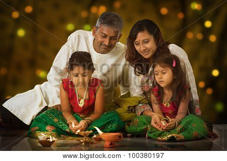 Indian family in traditional sari lighting oil lamp and celebrating Diwali, fesitval of lights inside a temple. Little girl hands holding oil lamp indoors.