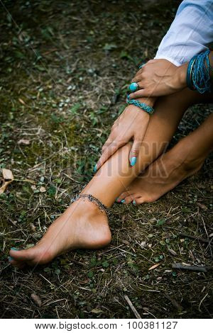 young woman hands and barefoot legs with lot of turquoise bijou, above view, natural light, selective focus