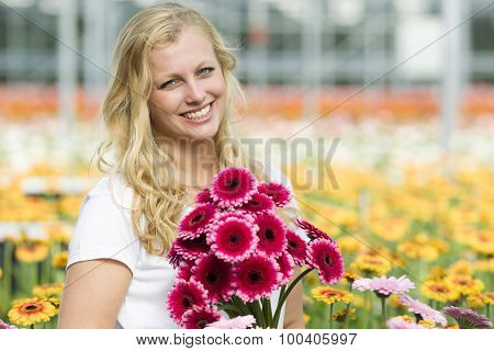 Young woman working in a greenhouse full of flowers.