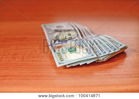 Stacks of one hundred dollars banknotes on wooden desk. Macro