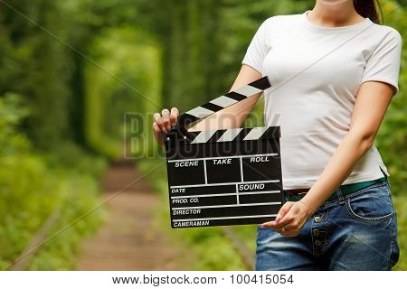 Woman Holding Clapper Board In Her Hands. Tunnel Of Love In Ukraine