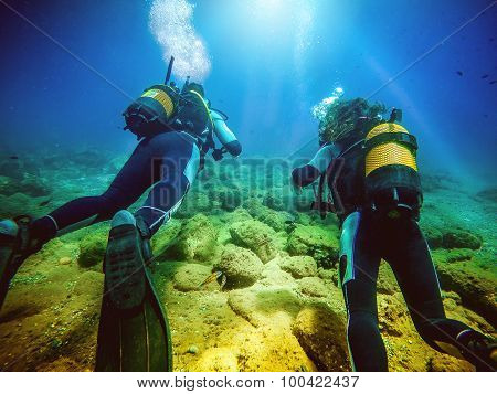 Two Divers Swimming Away From Camera.