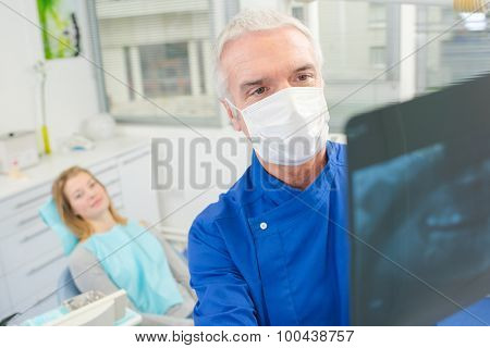 Male dentist looking at an xray