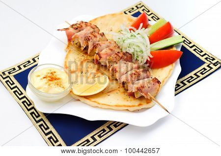 Souvlaki, kebab, grilled meat on pita bread with sauce, tomatoes and cucumbers, white plate.