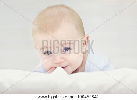 Adorable smiling baby lying in the bed