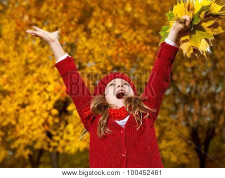 attractive young caucasian little girl in warm red colorful clothing  on yellow leaves outdoors smiling happy child kid walk looking up