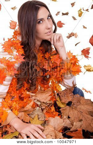 Attractive  Woman In A  Pile Of Autumn Leaves
