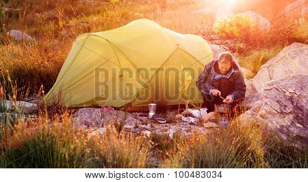 Adventure camping man cooking alone outdoors with tent, sunrise and lens flare in the mountain morning sunlight. Happy explorer enjoying a meal in the wilderness poster