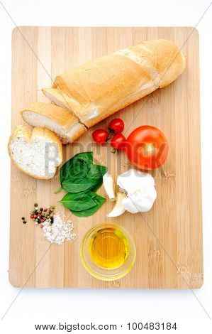 Loaf of baguette, tomatoes, basil, garlic and olive oil on a wooden chopping board, representing the raw ingredients of bruschetta, a famous Italian appetiser