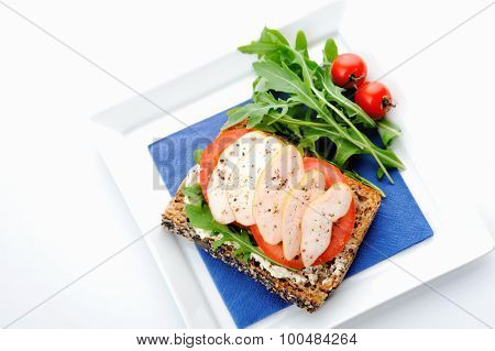 Seeded wholewheat toast topped with salad and smoked chicken