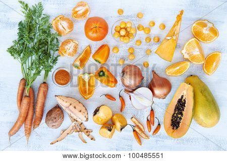 Selection of assorted fresh orange toned vegetables and fruit raw produce on white rustic background, pumpkin butternut carrot papaya pawpaw capsicum pepper sweet potato cherry tomatoes chilli orange