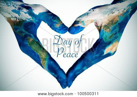 the hands of a young woman forming a heart patterned with a world map (furnished by NASA) and the text day of peace, slight vignette added