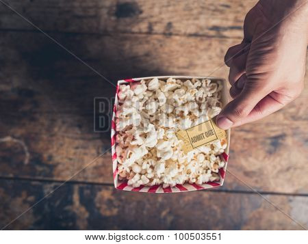 Hand With Ticket And Popcorn
