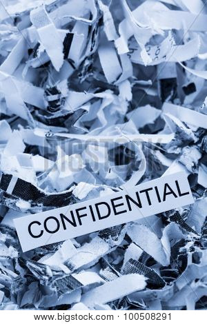 papierschnitzel tagged confidential, symbol photo for data destruction, banking secrecy and confidentiality