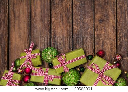 Rustic and antique wooden background with red and green christmas presents.