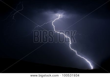 Bright lightning bolt on mountain with radio tower for power and communications