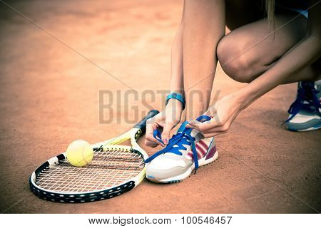 Tennis player tying shoelaces outdoors