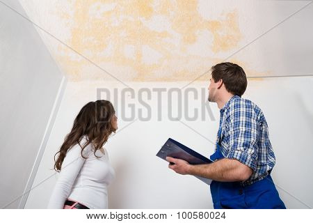 Worker Writing On Clipboard With Woman In House