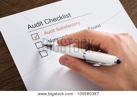 Person Filling Audit Checklist Form At Desk