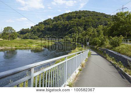 The bike lane leads along the River Ruhr below the Castle Isenburg in Hattingen (Germany Northrhine Westphalia Ruhr Area). poster