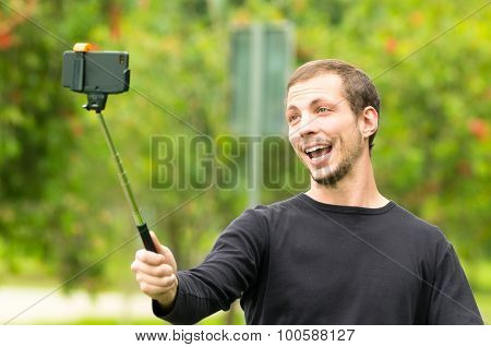 Hispanic man posing with selfie stick in park environment smiling happily