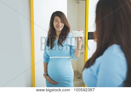 Asian Pregnant Woman Taking Picture Of Her Self In The Mirror