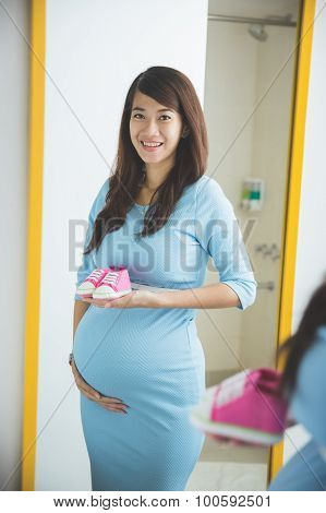 Pregnant Woman Smiling In Front Of A Mirror, Holding A Pair Of Baby Shoes