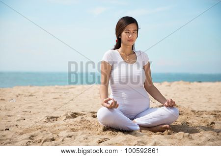 Pregnant Asian Woman Doing Yoga In The Sea Shore