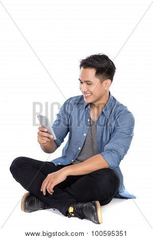 Young Asian Man Look At The Handphone While Sitting On The Floor, Isolated