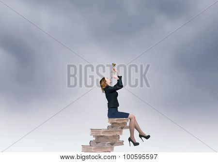 Young businesswoman sitting on pile of books proclaiming something in horn