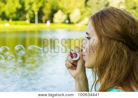 Beautiful Woman Blowing Bubbles In The Summe Near The Lake, Outdoors