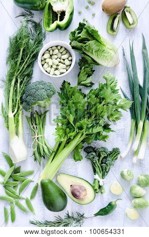Collection of green vegetables on rustic white background from overhead, broccoli, celery, avocado, brussel sprouts, kiwi, pepper, peas, beans, lettuce, poster