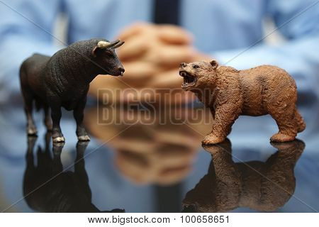 Businessman Is Watching Bull And Bear , Concept Of Stock Market And Investing