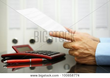 Businessman Is Reading  And Checking Financial Document With Binders,calculator  In Background