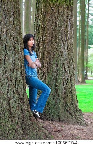 Young Teen Girl Leaning Against Large Pine Tree Trunk, Sad