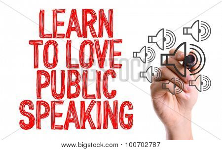 Hand with marker writing the word Learn to Love Public Speaking