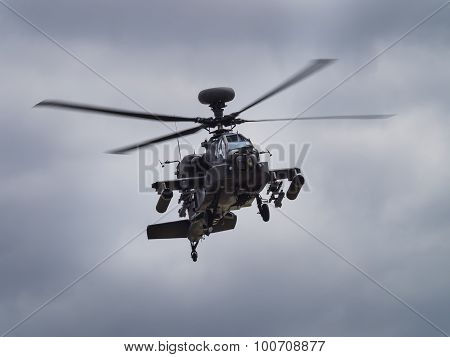 An Apache attack helicopter in mid flight poster