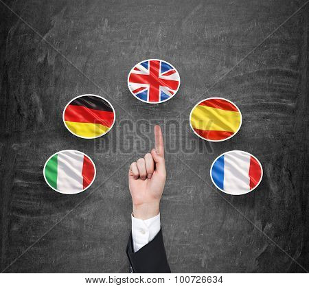 A concept of foreign language studying process. A finger is pointing out the Unites Kingdom flag as a priority in choice of foreign languages. Black chalkboard background. poster